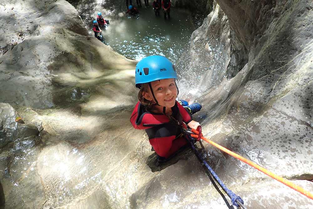 enfant qui descend en canyoing une cascade à annecy