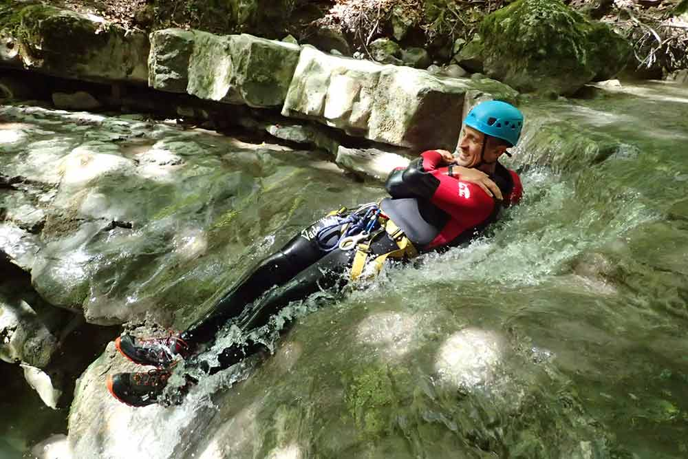 homme qui glisse au canyoning angon