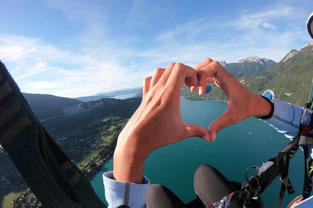 un coeur formé par les doigts en parapente à Annecy