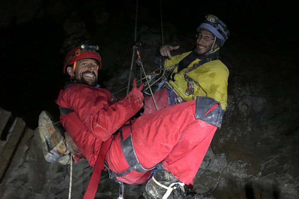 deux hommes remontent sur corde en spéléologie en haute savoie