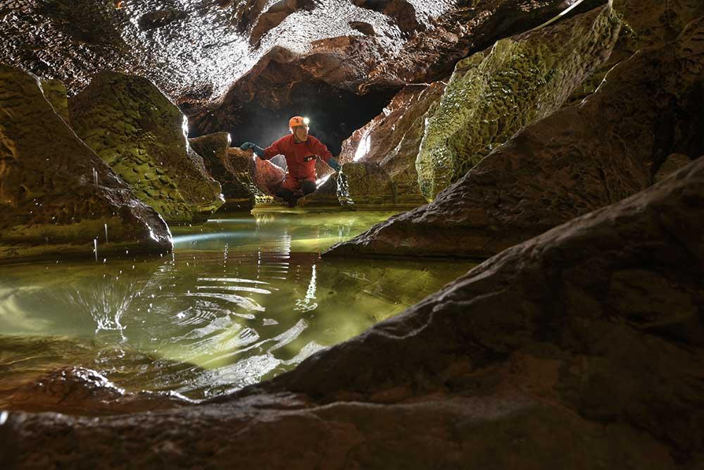 homme en spéléologia à annecy devant des trous d'eau