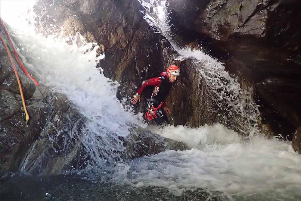 homme dans une cascade canyoning eaux rousses