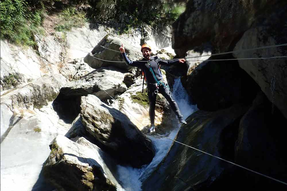 homme sur un pont de singe canyoning des eaux rousses